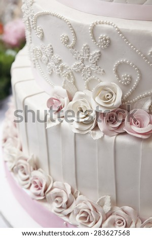 Close up white wedding cake decorate with roses and pearl - stock photo