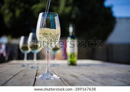 Close up wide angle  shot of a glass of white whine on a rustic table outside with natural light - stock photo