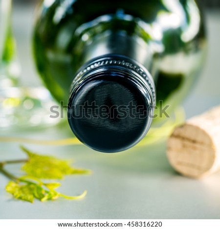 Close up wine Bottle with grape vine and wine cork on white table. Shallow depth of field . Dinning and Wining concept . - stock photo