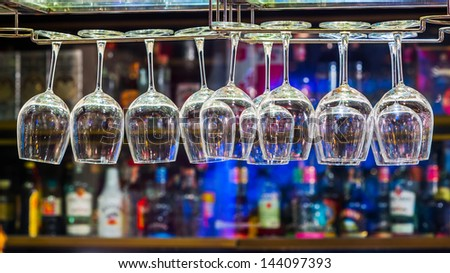 Close up wine glass on rack above counter bar