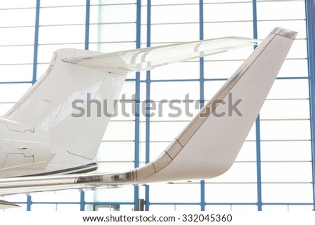 Close up wing and engine detail on an executive corporate jet parked in a hangar at an airport in an aviation, travel and transport concept - stock photo