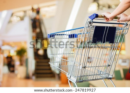 close up woman and shopping cart shopping mall