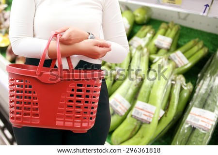 close up woman Asian with shopping basket and buy vegetable/fruit at supermarket/mall