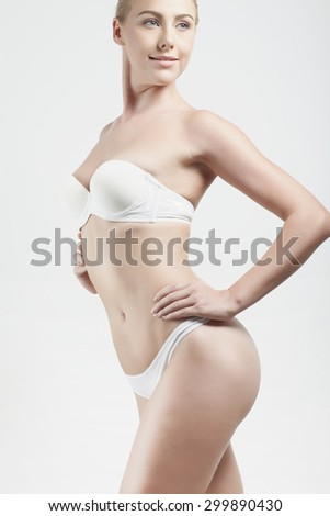 Close up woman body in white lingerie against white background - stock photo