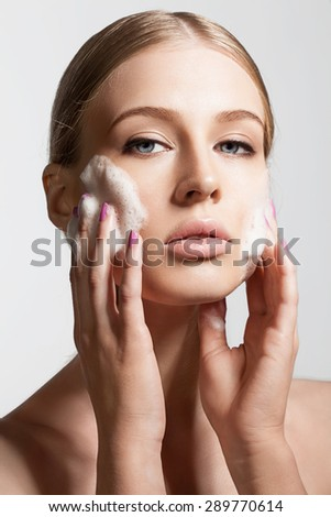 Close-up woman clears skin foam on a gray background - stock photo
