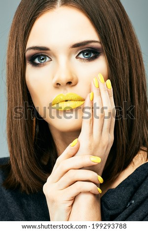 Close up woman face. Glamour make up portrait.Yellow lips and nails. - stock photo