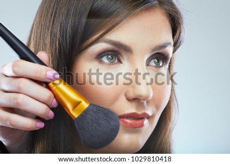 Close up woman face with make up brush. Bueuty style isolated portrait.