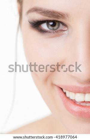 Close-up woman face with smoky eye's make-up smiling - stock photo