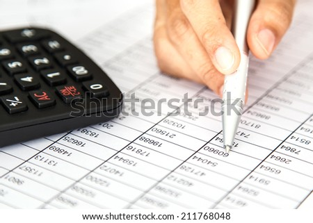 Close up woman hand holding pen on spreadsheet - stock photo