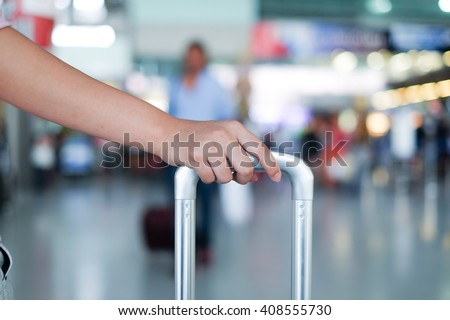 close up woman hand touching baggage for check in at counter in airport:tourism girl travel in holiday:teenager planning tour for make a trip and now she going aboard concept:departure arrival flight - stock photo