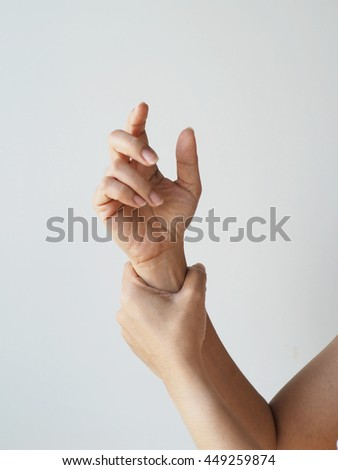 Close up woman having pain in injured wrist on white background, wrist pain concept.