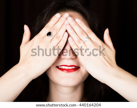 Close-up woman looks straight into the camera on a black background. laughing woman covering her eyes with her hand. expresses different emotions - stock photo