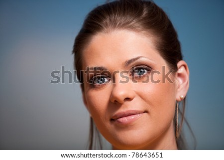 Close-up woman portrait. Blue eyes. Light make-up. Beautiful face on summer sky background . - stock photo