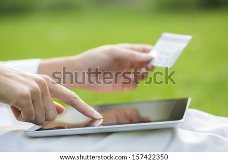 Close-up woman's hands holding a credit card and using tablet pc, online shopping, outdoor - stock photo