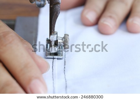 Close up woman working with sewing machine.