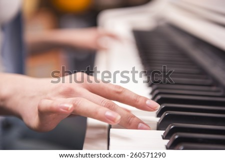Close-up. Women hands are playing the piano. Blurred background. - stock photo