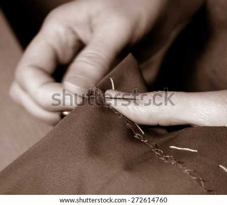 close up women's hand sewing monochrome       - stock photo