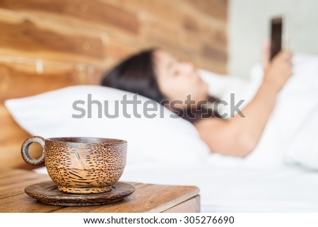 Close up wood coffee cup on table and women using smartphone on the bed