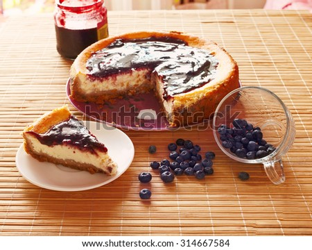 Close up wood table with cheeseckae on the platte with blueberry jam and bluberrys - stock photo