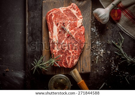 Close up Wooden Chopping Board with Raw Beef Meat on a Rustic Table with Herbs and Spices - stock photo