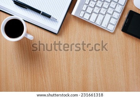Close up Wooden Table of Businessman with Notebook and Pen, Computer Keyboard, Mobile Phone and A Cup of Black Coffee to Stay as Stress Reliever. - stock photo