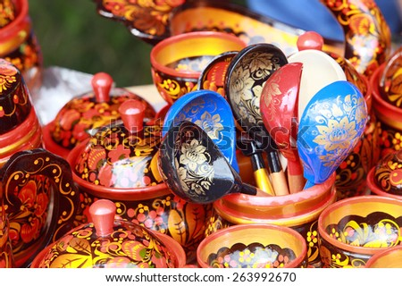 Close-up wooden utensils painted in Khokhloma style at the fair in the summer - stock photo