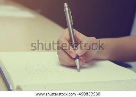 close up work woman writing homework solution on notebook paper page at classroom,student girl doing lecture note the lesson or researching about project:busy people:vintage mood tone color effect. - stock photo
