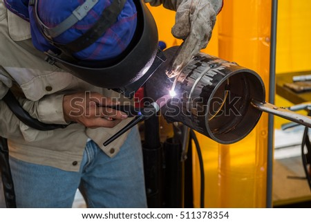 Close up worker use machine cutting steel in a factory. Industrial worker welding metal with many sharp sparks and worker during use electric wheel grinding