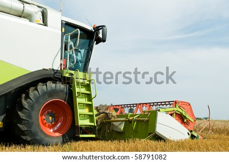 Close-up working harvesting combine in the field of wheat cereals - stock photo