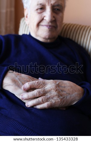 close up wrinkled hands of a senior person resting in an armchair - stock photo