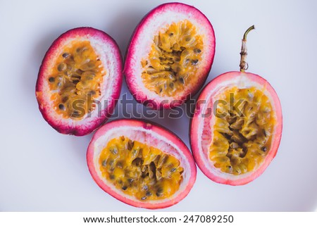 Close up yellow color passion fruit (maracuya) pulp and seed in small ceramic bowl isolated on BROWN board, spoon, spices - stock photo