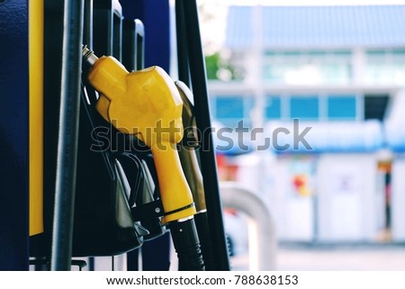close up yellow nozzle fuel in pump gas station with copy space background for text, saving money and energy for transport, manage for sucess business and industry concept, process vintage tone