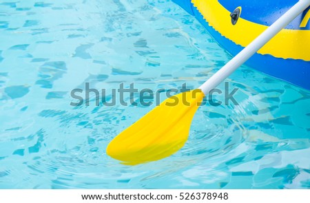 Close up yellow paddle, boat in blue swimming pool.