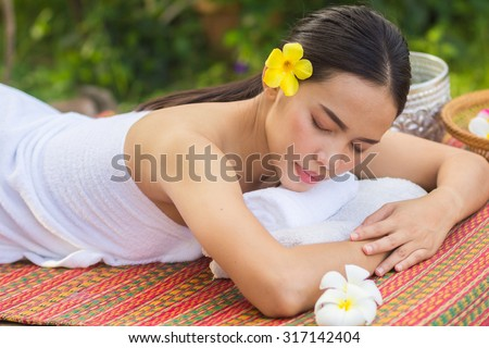 close up young beautiful asian woman lying for massage :Thai woman in spa treatment :woman relaxing wellness concept.natural outdoors spa treatment concept.healthy life concept.selective focused. - stock photo
