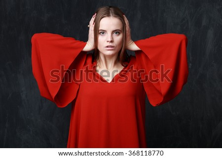 Close up young beautiful woman in res dress with wide sleeves, dramatic pose, hands on the ears, mouth is slightly opened, gray background - stock photo