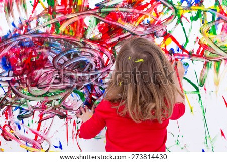 Close up Young Blond Kid Painting Abstract Design Using Various Colors on White Wall During her Painting Time. - stock photo