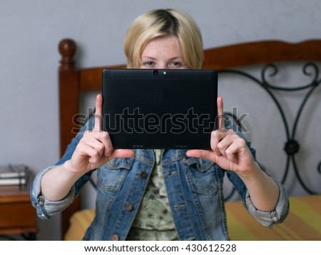 Close up young blonde woman holding a tablet and smiling, looking at the screen, sitting on the bed in the room - stock photo
