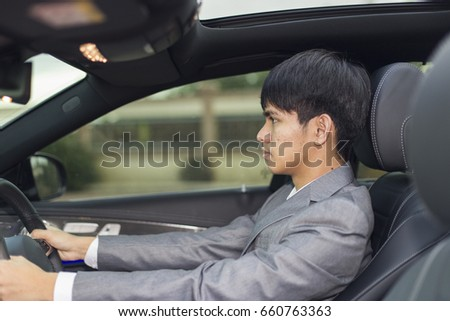 Close up young business man driving the car