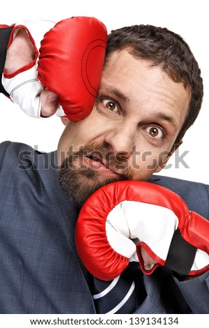 Close-up young businessman struck in the face by hands in boxing gloves isolated on white background