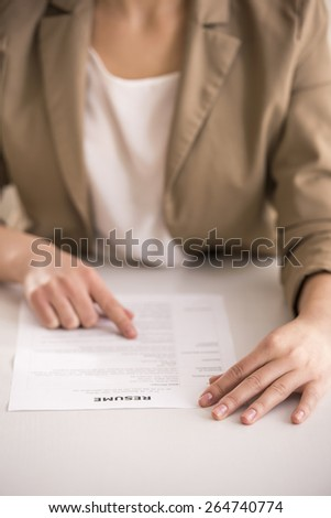 Close-up. Young businesswoman analyzing resume at desk in office. - stock photo