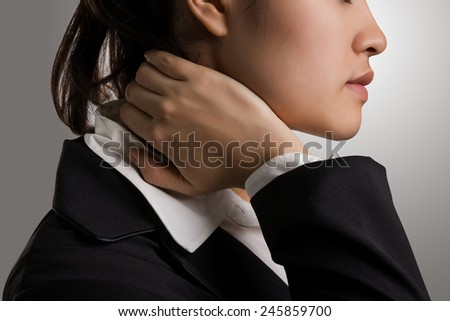 Close up young businesswoman in black suit holding hand on the pained neck. - stock photo