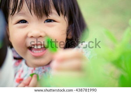 Close up Young child holding a plant in her hand,Little asian girl holding green leaf and smile.
