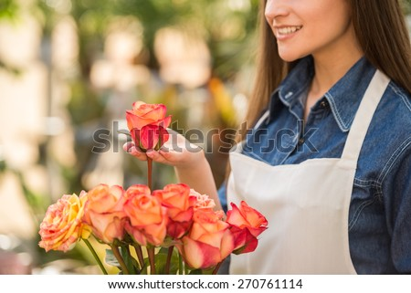 Close-up. Young female florist holding a rose in flower shop. - stock photo