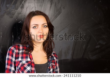 Close up Young Female in Checkered Shirt in Front Black Chalkboard While Looking at the Camera. Emphasizing Copy Space. - stock photo
