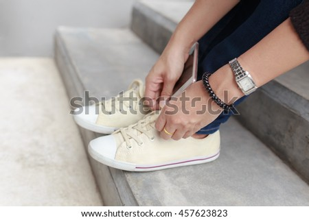 Close up young girl tying white shoe laces, Urban women fashion lifestyle