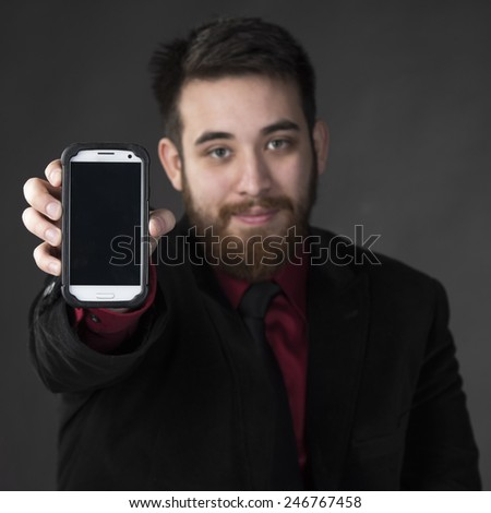 Close up Young Goatee Businessman Showing his Smart Phone While Looking at the Camera. Emphasizing Copy Space on Screen. Isolated on Gray Background - stock photo