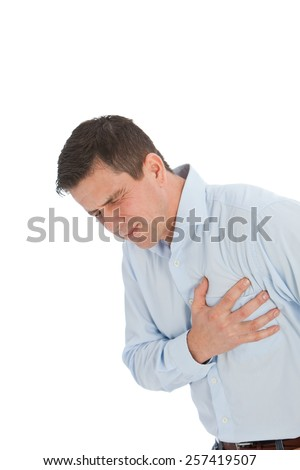 Close up Young Handsome Businessman Holding his Chest While Suffering From Angina Problem, Isolated on a White Background.