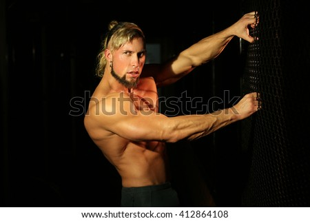 Close up young handsome muscular man near fence of grid