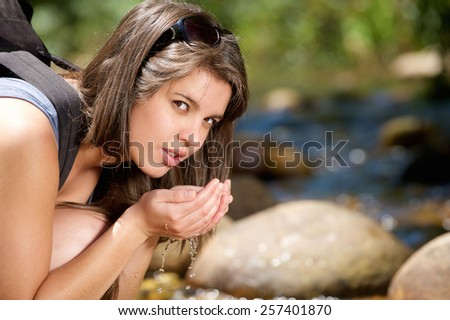 Close up young hiking woman drinking pure water from stream - stock photo