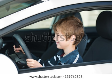 Close up young little boy driving a luxury car